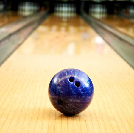 Bowling ball in an alley heading towards the pins  photo