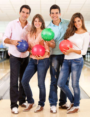 bowling alley: Happy group of friends bowling and holding balls