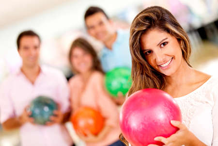bowling: Beautiful woman bowling holding a ball with friends and smiling