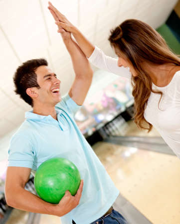 recreational sports: Happy team winning at bowling and giving a high-five