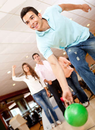 bowling alley: Man bowling and his friends cheering at the background