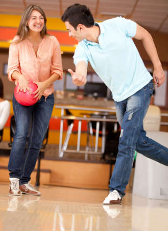 bowling: Couple bowling with a man teaching a woman how to swing