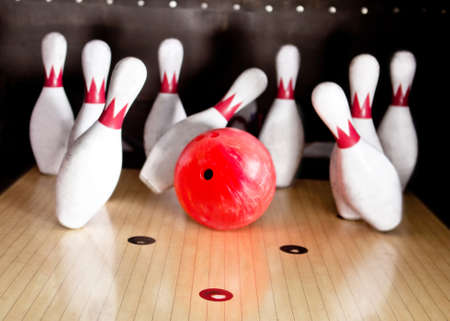 red pin: Bowling strike - ball hitting pins in the alley