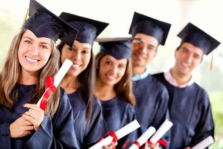 graduacion de universidad: Grupo de estudiantes de posgrado que sostienen su diploma despu�s de la graduaci�n