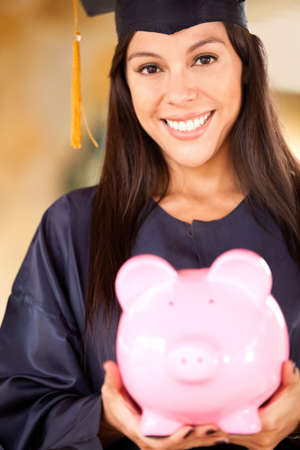 college fund savings: Graduate woman holding a piggybank with her education savings Stock Photo