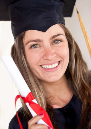 Beautiful female graduate holding her diploma and smiling  photo