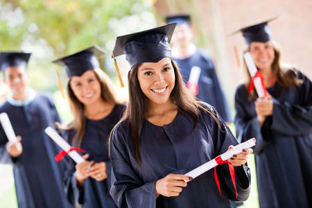 college graduate: Group of people in their graduation day wearing a gown and mortarboard Stock Photo