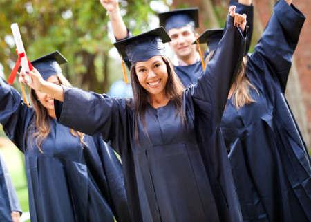 graduacion de universidad: Feliz grupo de estudiantes con los brazos arriba en su graduación