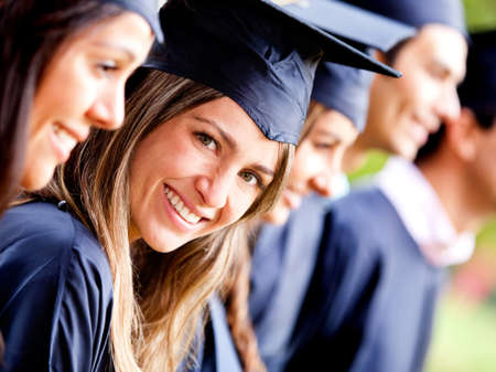 Woman standing out from a graduation group smiling  photo