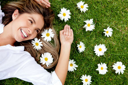 human hair: Beautiful woman lying on a flower granden enjoying her time outdoors