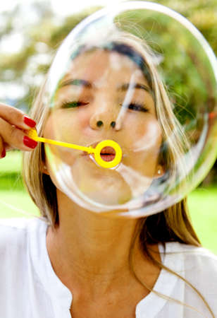 Woman portrait blowing bubbles and having fun - outdoors  photo