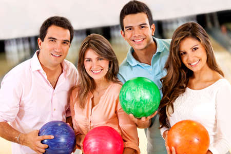 Happy group of friends bowling and holding balls photo