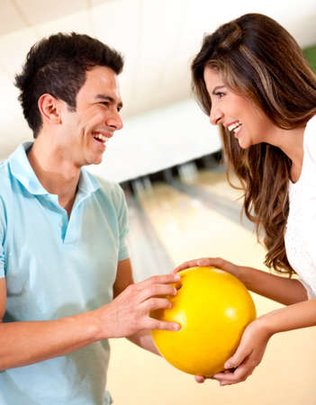 bowling alley: Couple going bowling for a date frirting and smiling
