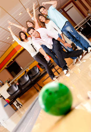 bowling: Man bowling and people cheering at the background Stock Photo