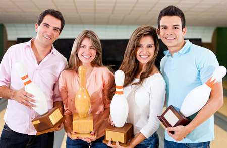 Happy group of friends winning a bowling trophy  photo