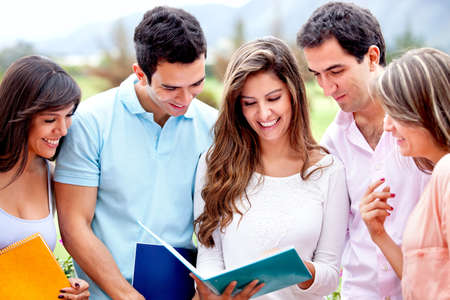 hispanic student: Feliz grupo de alumnos mirando una al aire libre los port�tiles