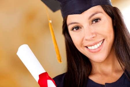 egresado: Hermosa mujer la celebraci�n de graduaci�n de su diploma y sonriente