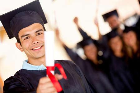 gorros de graduacion: Feliz graduado masculino que sostiene su diploma y sonriente