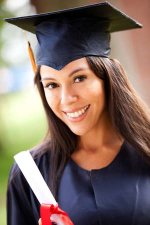 Beautiful female graduate wearing a graduation gown  photo