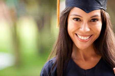 Beautiful woman graduating holding her diploma and smiling photo