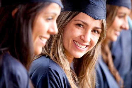 toga y birrete: Hermosa mujer graduada de pie fuera de un grupo de estudiantes Foto de archivo