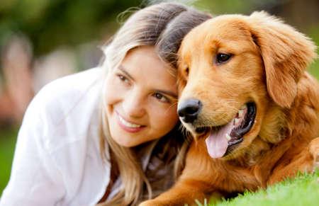 mejores amigas: Retrato de una mujer con su hermoso perro tumbado al aire libre