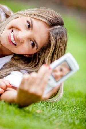 Woman taking a self-portrait with the camera on her cell phone photo