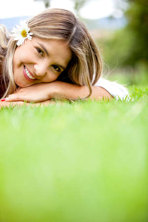dasiy: Cute woman with a dasiy on her head lying on the floor - outdoors