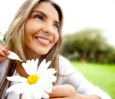 Woman outdoors holding a flower playing he loves me or not  photo