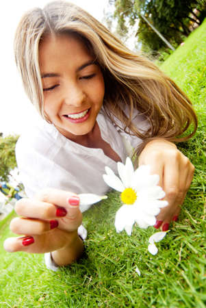 detach: Woman in love holding a daisy and playing loves me or not Stock Photo