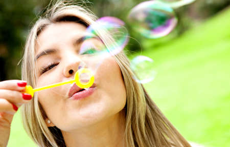 Woman blowing soap bubbles with a wand at the park  Stock Photo - 12393638