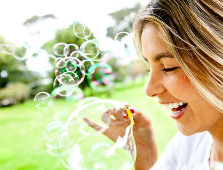 blowing bubbles: Happy woman portrait blowing soap bubbles at the park  Stock Photo