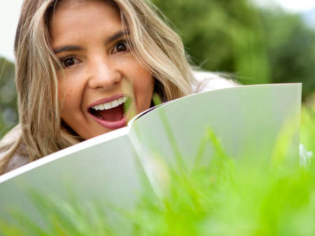 Beautiful woman reading outdoors and looking surprised  photo