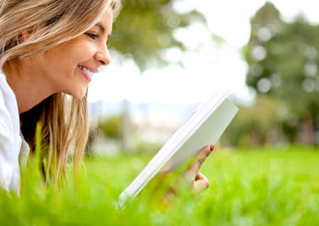 Beautiful woman reading a book at the park  photo