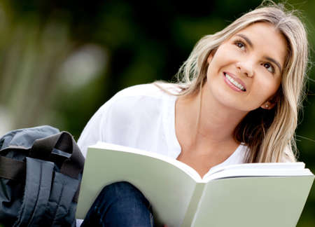 Pensive woman studying outdoors and holding a book  photo