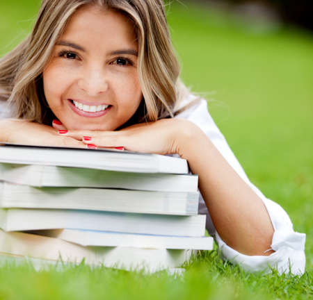 Beautiful female student with books at the park  photo