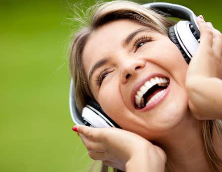 escuchando musica: Retrato de mujer feliz con auriculares escuchando la música