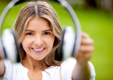 Woman portrait holding big headphones and smiling outdoors  photo