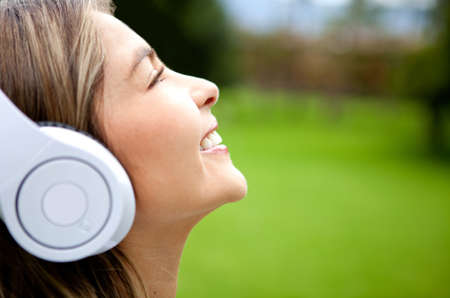 Happy woman listening to music outdoors wearing headphones  photo