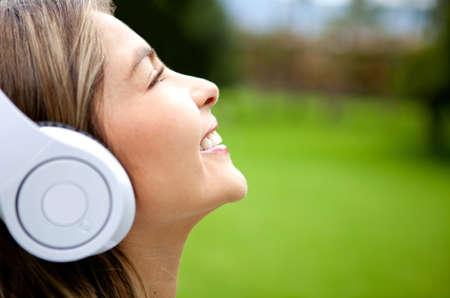 audifonos: Mujer feliz escuchando m�sica al aire libre, el uso de auriculares Foto de archivo