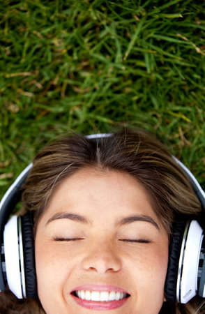 Woman lying on the grass with headphones photo