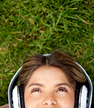 escuchando musica: Mujer tendida en la hierba con los auriculares Foto de archivo