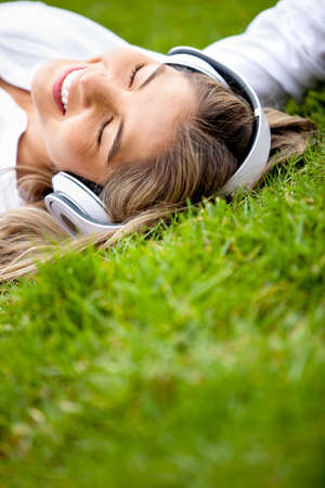 Girl lying at the park relaxing with music photo