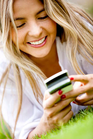 Happy woman texting on her cell phone outdoors  photo