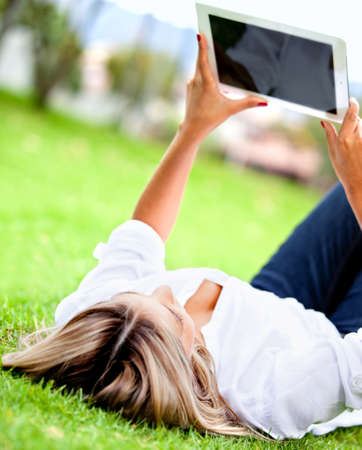 Woman lying outdoors reading on a tablet computer  photo