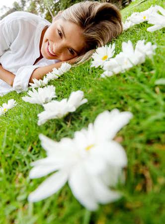 quiet adult: Bella donna sdraiata su un giardino fiorito pieno di margherite Archivio Fotografico