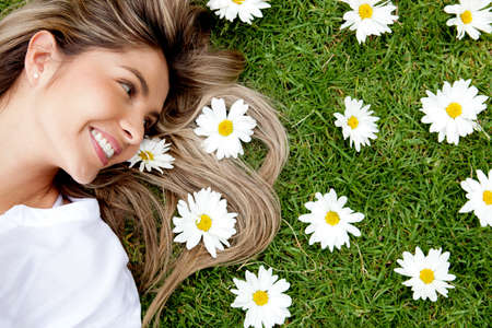 Beautiful woman lying in a garden of flowers   photo