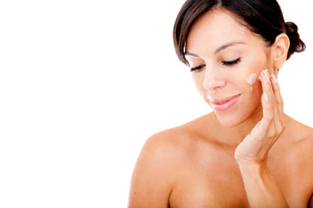 moisturize: Beauty woman applying face cream - isolated over a white background