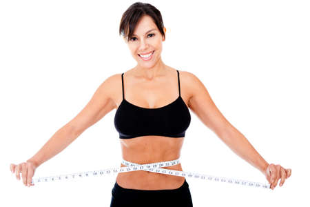 Woman loosing weight measuring her waist - isolated over a white background photo