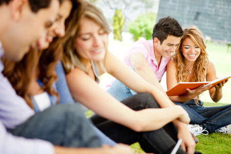 Happy group of young student sitting outdoors   photo